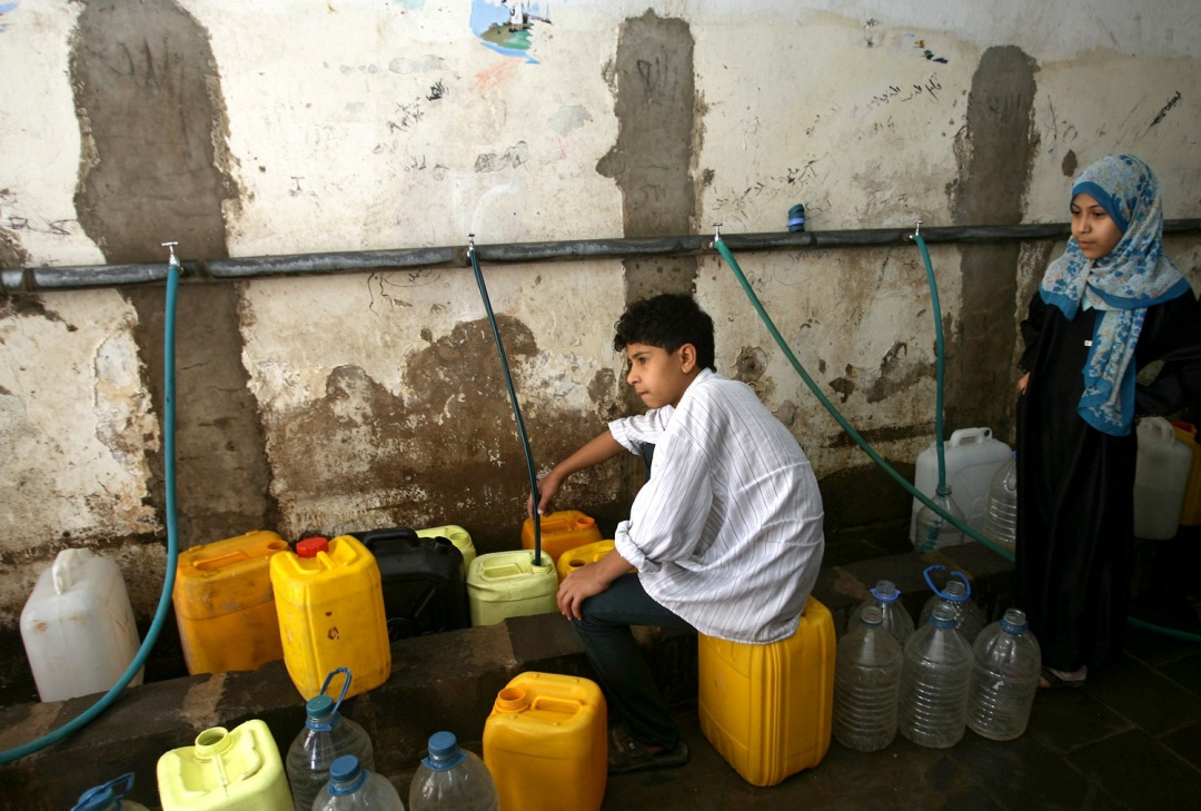 Image: Yemeni children fill water from public taps in Sanaa